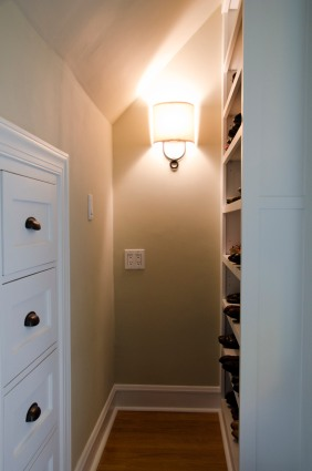 Custom shoe cabinet and built-in drawers in unused space over a stairwell crafted by a local millworker, Crossroads Construction.