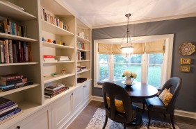 Custom built-in bookshelf and limestone mosaic tile floor. The round table is espresso-stained bamboo. The chairs from Oly Studio are upholstered in slate leather. The window seat is Massive Paisley fabric by Maharam. Custom roman shades are in a gold silk.