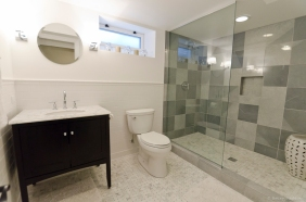 The blue-gray Bardiglio Imperiale marble in the shower is from Italy. The floor is a carrara basket-weave mosaic. The white, subway tile is Daltile. Toilet, carrara marble vanity and Purist fixtures are all Kohler. The Asian ceramic garden stool is from Jayson Home.