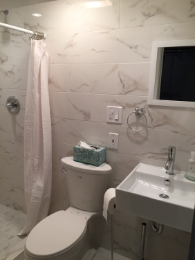 Bathroom with marble-look porcelain tile walls and floor